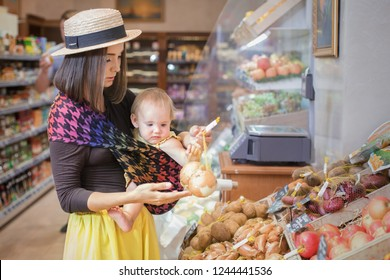 A young mother carrying her little baby in a sling  at a grocery store buying a health food.  Vegetables, backery  in russian language.