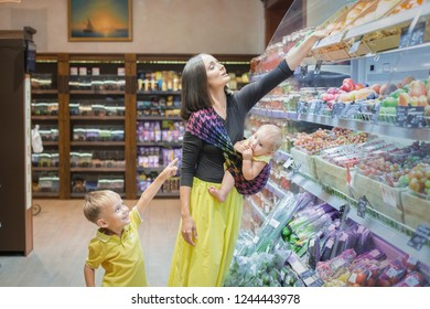 A young mother carrying her little baby in a sling with a kid son at a grocery store buying a health food.  Vegetables, backery  in russian language.