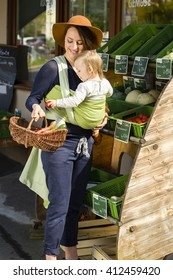 A young mother carrying her little baby in a sling before belly and buys vegetables at a market stall of a Health Food Shop. She holds a wicker basket in hand and the baby grabs vegetables in basket.