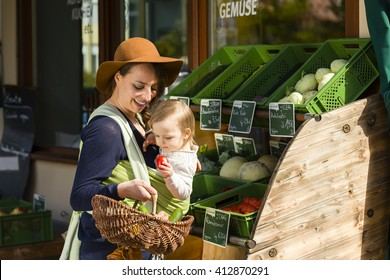 A young mother carrying her little baby in a sling before belly and buys vegetables at a market stall of a Health Food Shop.  Milk, cheese, eggs, sausage, vegetables in german language