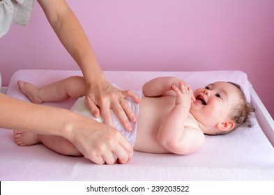 Young mother changes her baby (girl age 06 months) nappy. Concept photo parenthood and motherhood.