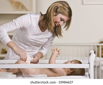 A young mother is changing her baby's diaper.  She is smiling and looking at her baby.  Horizontally framed shot.