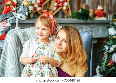 Young mother with child Christmas morning. Concept of Merry Christmas, New Year, holiday, winter, traditions.