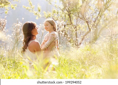 Young mother and child daughter together, hugging and smiling sitting and relaxing in a golden field of sunshine and spring flowers while on a summer holiday. Family activities and outdoors lifestyle.