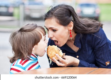 Young mother with child eating a hamburger  on the street