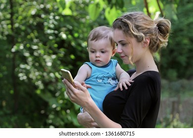 Young mother with a child in her arms shows him the phone