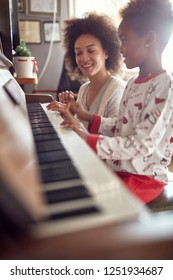 young mother with child on Christmas play music on piano. concept of holidays and family happiness.