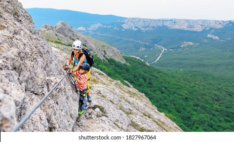 Young mother, child in safety equipment climb to mount top by via ferrata beginner route. Family travel adventure, hiking activity. Kids exploring nature on summer vacation. Weekend day walking tour