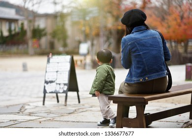 Young mother and child Sit and look at the autumn leaves change in autumn in Japan.