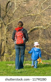 Young mother and child walking in spring forest, taken with shallow depth of field