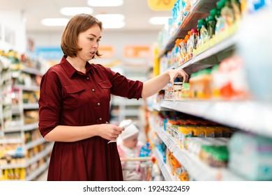 Eine junge Mutter wählt Babynahrung in einem Supermarktregal. Im Hintergrund, unscharf, sitzt ein Kleinkind in einem Einkaufswagen. Das Konzept des Einkaufs mit Kindern