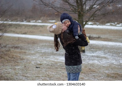young mother with closed eyes holding and kissing her son very adorable babyboy outside in winter