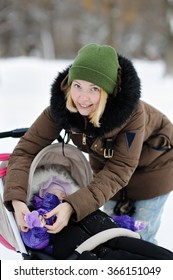 Young mother clothe warm mitten at her little daughter in winter park