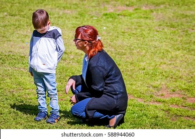 Young mother comforting her upset little child outside stock image. Illustrative