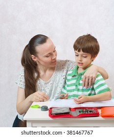 A young mother controls her six years old child's homework. White background