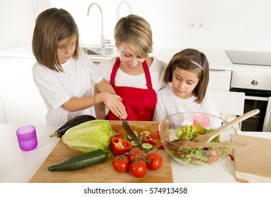 young mother in cook apron and sweet beautiful twin daughters cooking preparing together salad playful at home kitchen in healthy vegetable nutrition and homecook concept