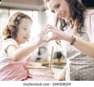 Young mother cooking with her little daughter