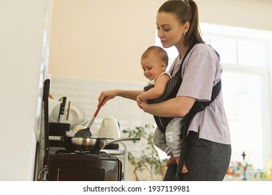 A young mother cooks in the kitchen, the child is fastened to her chest with a baby carrier or babywearing system. The difficulties of motherhood. High quality photo
