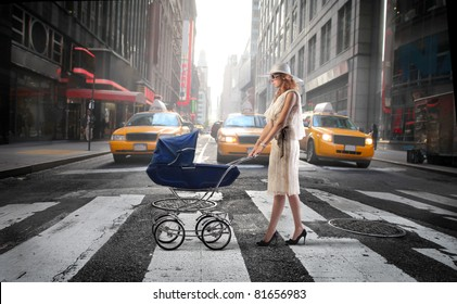 Young mother crossing a city street with a pram