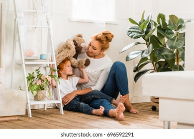 young mother and cute daughter playing together with teddy bear at home