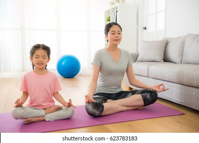 young mother with cute female children meditating and doing yoga exercise at home in the living room on the comfortable sunny day. family healthy lifestyle with sporting concept.