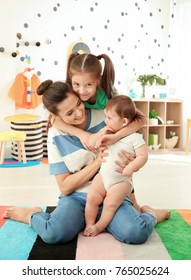 Young mother with cute kids in children room