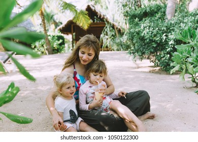 Young mother with cute little daughters relaxing at sandy tropic