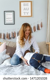 Young mother with a cute son having fun in the bedroom on the bed