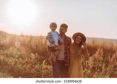 Young mother and dad playing, hugging, kissing with their little son in autumn field at sunset