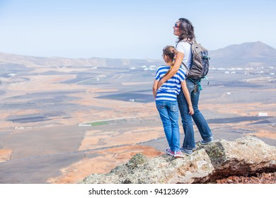 Young mother and daughter with backpack standing on cliff's edge and looking to a sky