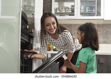 Young mother and daughter baking cupcakes together in kitchen
