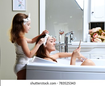 Young mother and daughter in a bathroom bath tub playing with mobile cell phone happy smiling