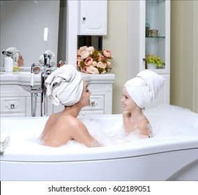 Young mother and daughter in a bathroom happy smiling taking bath with big soft white towels on a heads