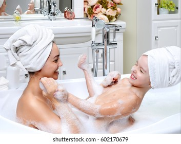 Young mother and daughter in a bathroom playing happy smiling hugging taking bath with foam