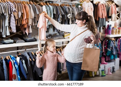 Young mother and daughter choose comfortable things for a baby girl in a clothing store