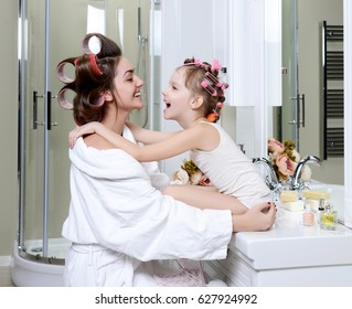 Young mother and daughter in curlers in a bathroom happy smiling hug each other family skin care concept in bath room