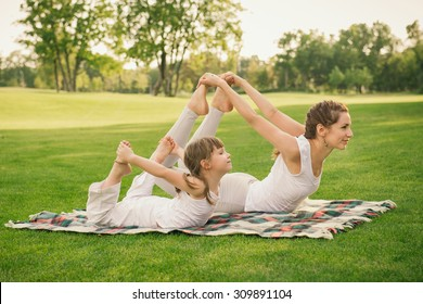 Young mother and daughter doing gymnastics and stretching in the city park on sunset