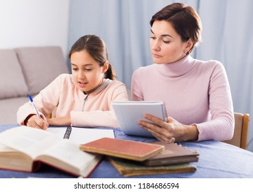 Young mother and daughter are doing school homework together at home