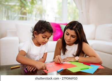Young mother and daughter drawing together