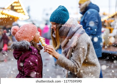 Young mother and daughter eating white chocolate covered fruits on skewer on traditional German Christmas market. Happy girl and woman on traditional family market in Germany, Munich during snowy day.