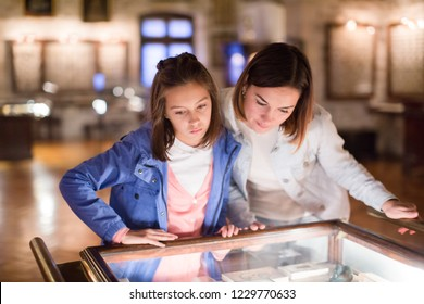 Young mother and daughter enjoying medieval expositions at a museum. Focus on both persons