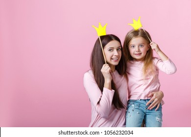 young mother and daughter having fun together and holding paper yellow crown on pink background