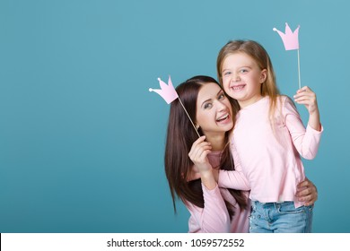 young mother and daughter having fun together and holding paper pink crown on blue background