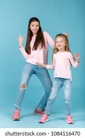young mother and daughter having fun together and dancing