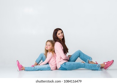 young mother and daughter having fun together on gray background