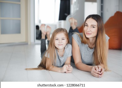 young mother with daughter having fun in living room at home. Woman and young preteen girl playing in white light room smiling, hugging. happy family