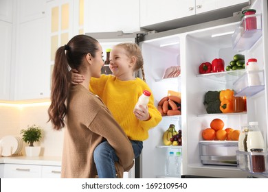 Young mother and daughter near open refrigerator in kitchen