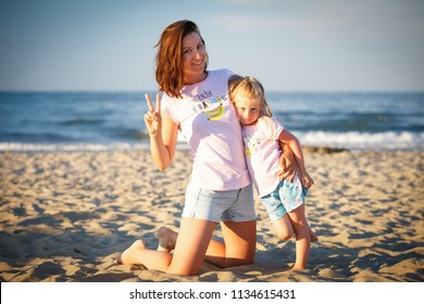 Young mother with daughter on beach on sea background at the sunset.
