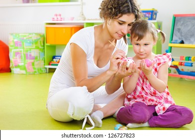 Young mother and daughter painting and decorating Easter eggs at home