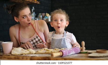 Young mother and daughter prepare cookies in kitchen. They are in aprons. Little girl and mother surprise and admiration. Positive emotions. Family time.